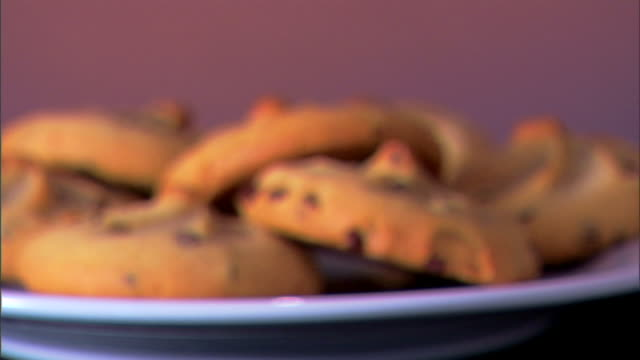 rack focus to a close-up of a plate of chocolate chip cookies rotating on a plate. - chocolate chip stock videos & royalty-free footage