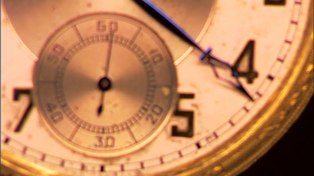 rack focus to an extreme close-up of the second hand of an antique pocket watch. - 懐中時計点の映像素材/bロール