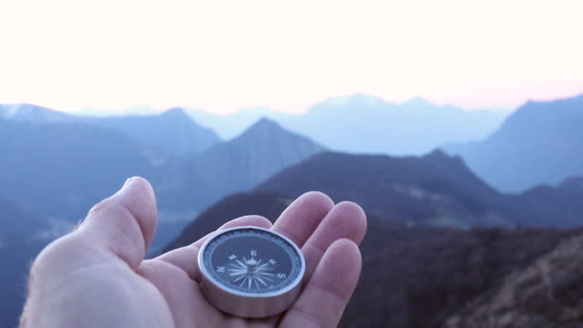Rack focus view of hand holding compass, above mountains