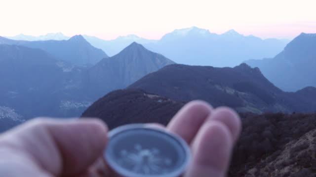 rack focus view of hand holding compass, above mountains - kompass stock-videos und b-roll-filmmaterial
