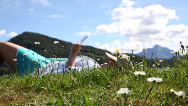 rack focus view of woman relaxing in mountain meadow, using digital tablet - reclining stock videos & royalty-free footage