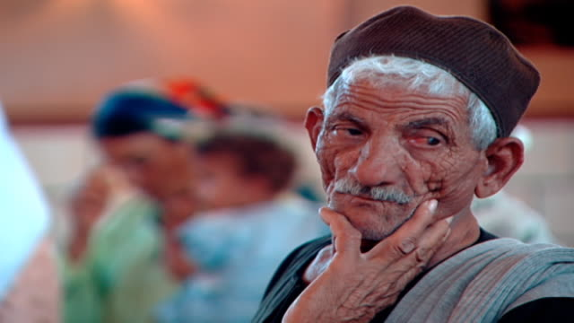 stockvideo's en b-roll-footage met rack focus view on a wizened old man and a female coptic worshipper carrying her infant and crossing herself in church - gelovige