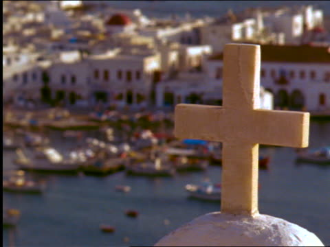 rack focus white cross to harbor + coastal town in background / Mykonos, Greece