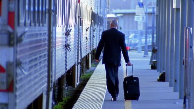Rack focus wide shot businessman walking quickly along platform towards commuter train / stepping aboard