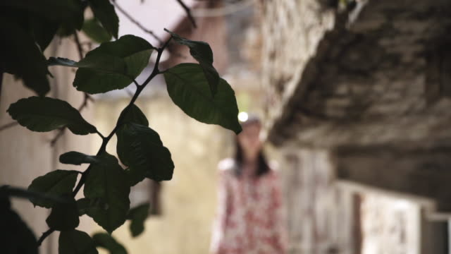 rack focus, woman walks down alleyway in crete - intoning bildbanksvideor och videomaterial från bakom kulisserna