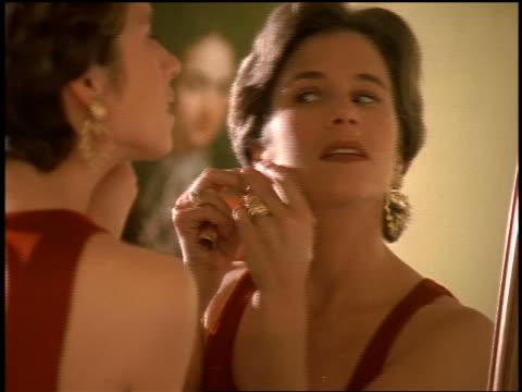 vídeos de stock, filmes e b-roll de rack focus woman wearing dress looking in mirror putting on earrings + applying lipstick - brinco
