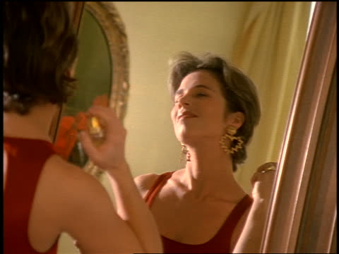 rack focus woman wearing dress looking in mirror putting on perfume