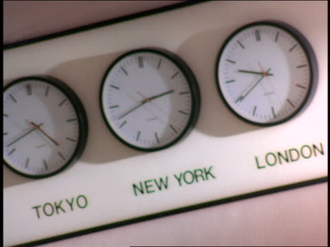 CANTED rack focus world time-zone clocks on wall / 'Tokyo',  'New York' + 'London'