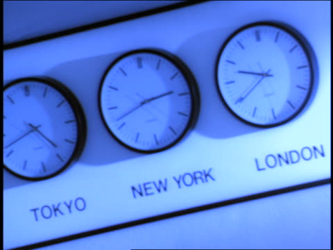 BLUE CANTED rack focus world time-zone clocks on wall / 'Tokyo', 'New York' + 'London'