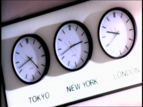 "OVEREXPOSED CANTED rack focus world time-zone clocks on wall  / ""Tokyo"", ""New York"" + ""London"""