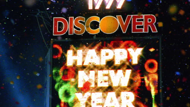 Rack focus zoom in 'Happy New Years!' sign with Discover logo and confetti in air / zoom out to reveal Times Square, New York City