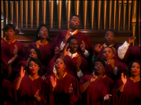 rack focus zoom out black gospel choir in robes singing + clapping in church / finish + talk - 賛美歌点の映像素材/bロール