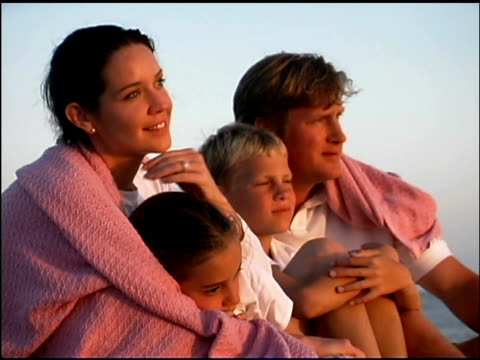 rack focus zoom out of a family sitting together outdoors watching the sunset. they have a blanket wrapped around them. - see other clips from this shoot 1135 stock videos & royalty-free footage