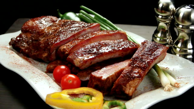 rack of ribs on platter with amenities. left rotation. - silver platter stock videos and b-roll footage