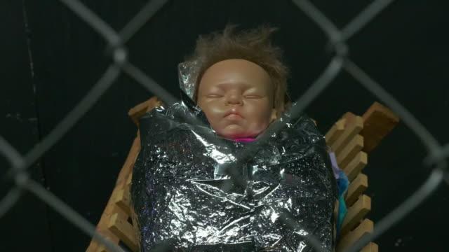 vídeos de stock e filmes b-roll de rack shot establishing shot of baby jesus in a cage in the border separation nativity scene in claremont united methodist church in california. - jaula