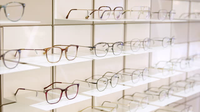 rack with frames for glasses in optical store - optical equipment stock videos & royalty-free footage