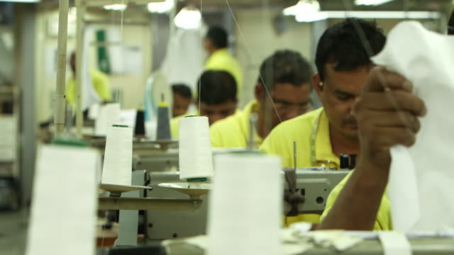 rackfocus from asian tailor's working electric sewing machines to cotton spools on a garment factory shopfloor - dish dash stock videos & royalty-free footage
