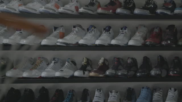 rack-focus from basketball hoop to air jordan sneakers on wall in shop - scarpe da ginnastica video stock e b–roll