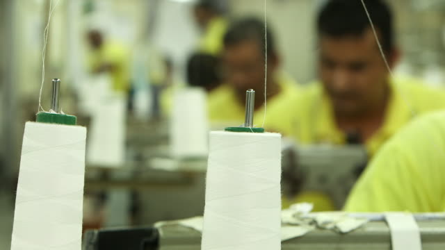 rack-focus from cotton spools for an electric sewing machine on a garment factory shop-floor to asian tailor's working electric sewing machines. - tailored clothing stock videos & royalty-free footage