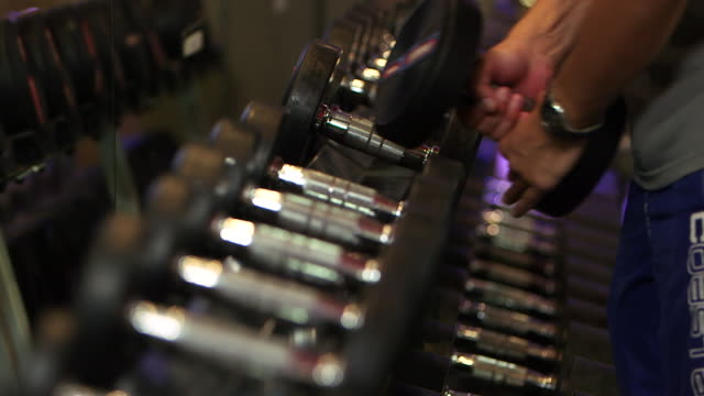 rack-focus of dumbbells as a man lifts his desired weights off the rack. - exercising stock videos & royalty-free footage