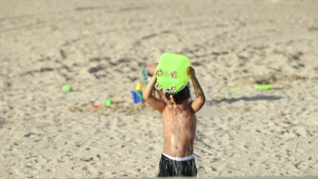 rack-focus on a small boy playing with his toys on a beach. - jiddah点の映像素材/bロール