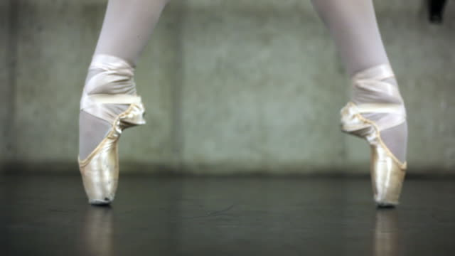 Rack-focus shot of a female ballet dancer's feet.