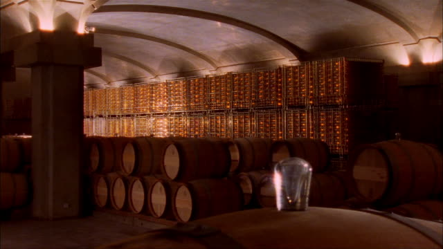Racks of wine bottles and casks of wine stacked in cellar at Chateau d'Yquem / Graves, Bordeaux, France