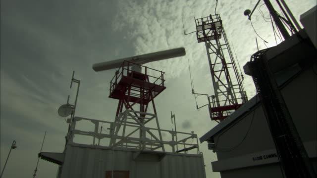 A radar antenna spins atop a tower.