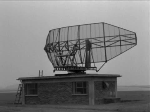 a radar dish turns near a runway at london airport - radar stock videos and b-roll footage