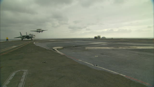 ms, pan, radar plane landing on aircraft carrier deck - aircraft carrier stock videos and b-roll footage