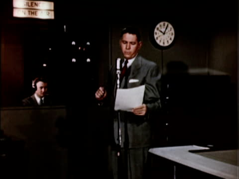 stockvideo's en b-roll-footage met 1956 ms radio announcer reading copy in front of studio microphone / usa - compleet pak