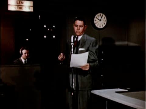 stockvideo's en b-roll-footage met 1956 ms radio announcer reading copy in front of studio microphone / usa - mid volwassen mannen