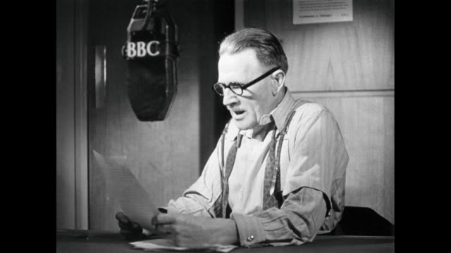 vídeos de stock, filmes e b-roll de recreation a bbc radio announcer reporting on the latest updates of the wwii war effort / england, united kingdom - 1946