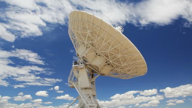 t/l radio antenna scans the sky, part of the very large array / new mexico, usa - astronomiskt teleskop bildbanksvideor och videomaterial från bakom kulisserna
