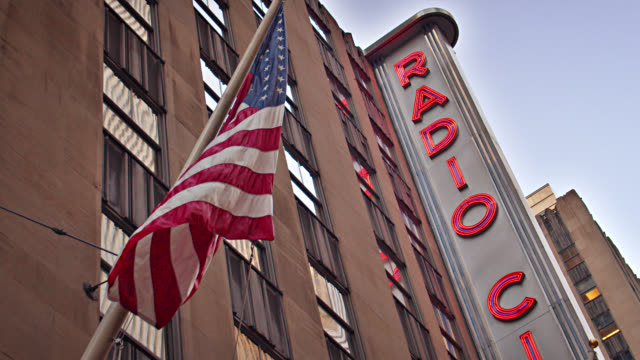 radio city hall. new york. american flag - rockefeller center video stock e b–roll