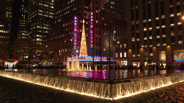 radio city music hall & 6th avenue fountain (night) - radio city music hall stock videos and b-roll footage