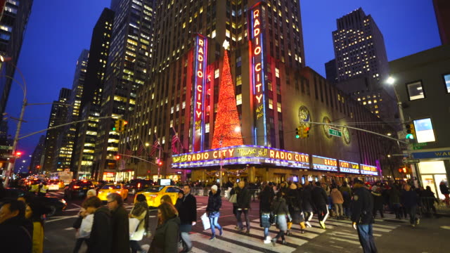 radio city music hall christmas tree glows in christmas colors and decorated with christmas decorations in the night at midtown manhattan new york city ny on jan. 02 2020. - radio city music hall stock videos & royalty-free footage