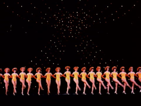 1960 MONTAGE Radio City Music Hall Rockettes performing in kick line on stage / New York City