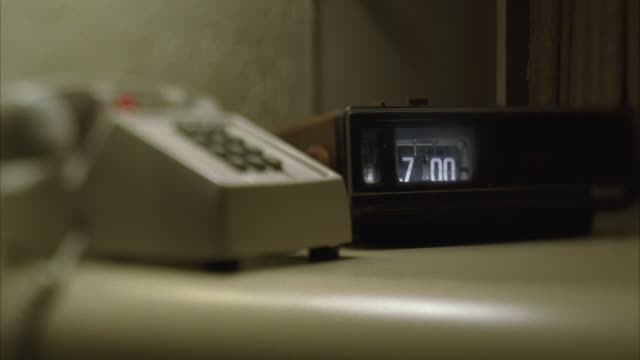 cu selective focus radio clock and telephone on table next to bed - landline phone stock videos & royalty-free footage