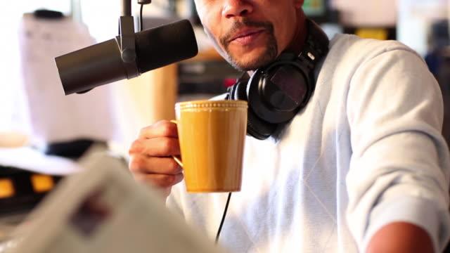 ms tu radio disc jockey reading news paper and talking in mic his studio / santa fe, new mexico, united states - radio jockey stock videos & royalty-free footage