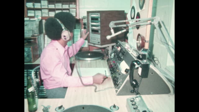 radio dj in studio spins records - ラジオ放送点の映像素材/bロール
