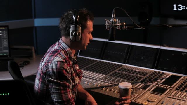 vídeos de stock, filmes e b-roll de dj apresentador de rádio controles operacionais em estúdio - rádio eletrônico de áudio