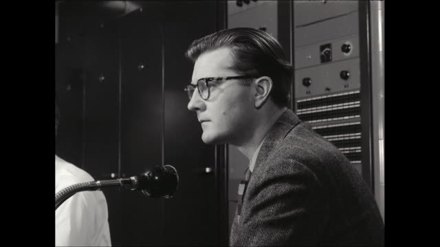 CU Radio presenter talking on microphone in radio broadcast studio / United States