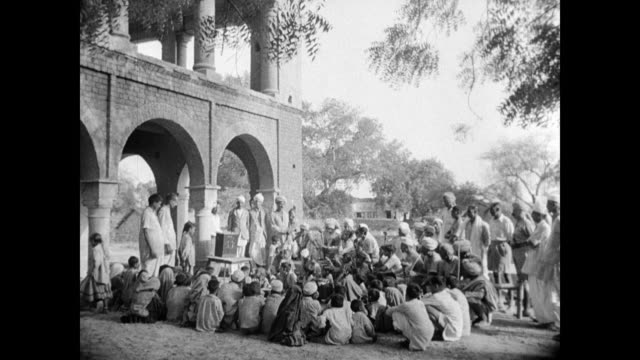 radio tower. male villagers gathered outdoors listening to 'air' all india radio community broadcast, vs village men holding male children. business:... - 1949 bildbanksvideor och videomaterial från bakom kulisserna