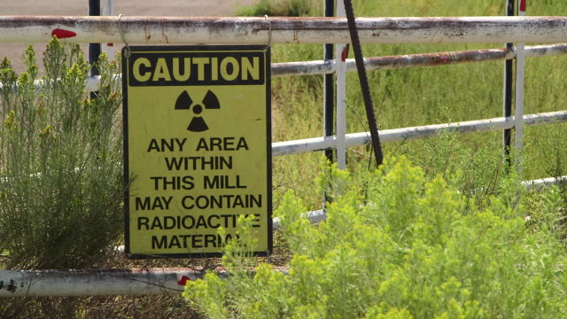 radioactive caution sign near windmill in new mexico, medium shot - radiation stock videos & royalty-free footage
