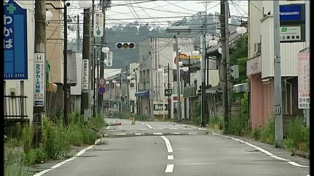 radioactive water leak from fukushima nuclear plant lib pov shot through front windscreen of car as along to nuclear checkpoint ext deserted village... - nuclear energy stock videos & royalty-free footage