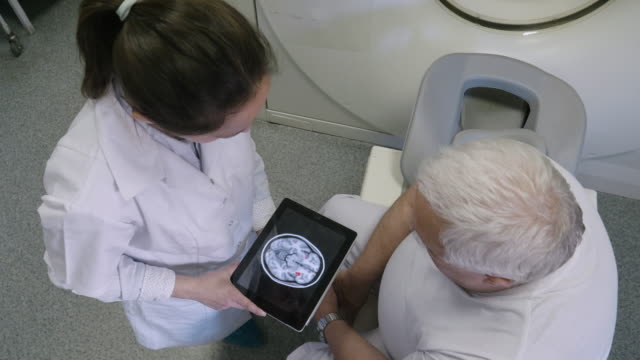 radiologist preparing the medical scanner for work. talking with the patient and helping him get ready for the procedure. - radiologist stock videos & royalty-free footage
