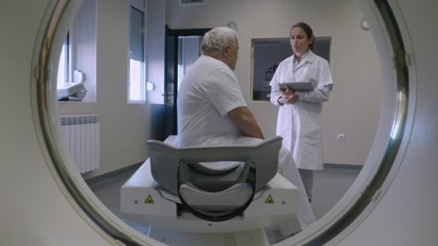 放射科醫生準備醫療掃描器工作。與病人交談,説明他為手術做好準備。 - 放射線 個影片檔及 b 捲影像