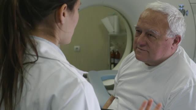 vídeos de stock, filmes e b-roll de radiologista preparando o scanner médico para o trabalho. conversando com o paciente e ajudando-o a se preparar para o procedimento. - tomografia