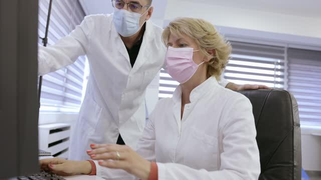 vídeos de stock, filmes e b-roll de radiologistas usando máscaras faciais protetoras e olhando para o monitor - tomografia